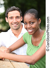 Mixed race couple sat at park table