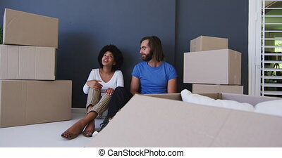 Mixed race couple sitting in between cardboard boxes at new apartment house
