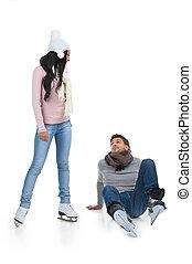 Mixed race couple skating at the skating rink. Man falling down while African girl teaching