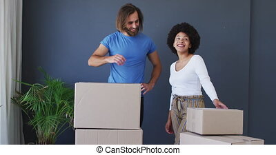 Mixed race couple standing in between cardboard boxes at new apartment house