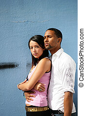 Mixed race couple stood by wall