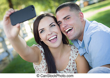 Mixed Race Couple Taking Self Portrait in Park - Happy Mixed...
