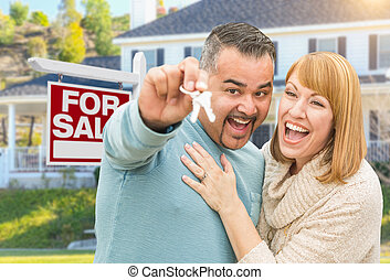 Mixed Race Couple With Keys in Front of Real Estate Sign and New House