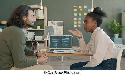 Mixed race creative team man and woman discussing business looking at laptop screen in office