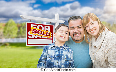 Mixed Race Family In Front of House and Sold For Sale Real Estate Sign