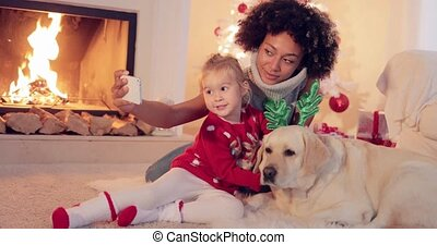 Mixed race family taking christmas selfie - Happy mixed race...