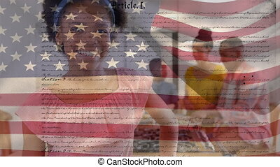 Animation of U.S. flag waving with U.S. Constitution text rolling over mixed race woman smiling with her family in the background. United States of America flag and holiday concept digital composition