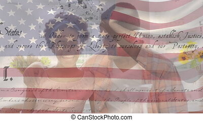 Animation of U.S. flag waving with U.S. Constitution text rolling over mixed race couple embracing. United States of America flag and holiday concept digital composition
