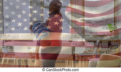 Animation of U.S. flag waving with U.S. Constitution text rolling over mixed race man playing with his son. United States of America flag and holiday concept digital composition