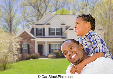 Mixed Race Father and Son In Front of House