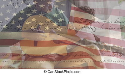Animation of U.S. flag waving with U.S. Constitution text rolling over mixed race man playing a guitar melody to his daughter. United States of America flag and holiday concept digital composition