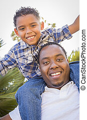 Mixed Race Father and Son Playing Piggyback in Park - Happy...
