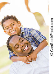 Mixed Race Father and Son Playing Piggyback in Park