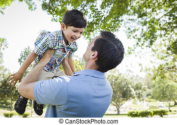 Father and Son Playing Together in the Park - Mixed Race...
