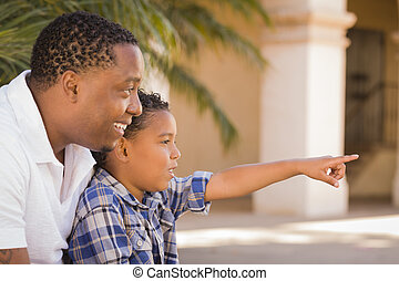 Mixed Race Father and Son Pointing in the Park - Happy...