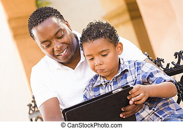 Mixed Race Father and Son Using Touch Pad Computer Tablet -...