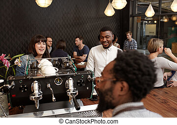 Mixed race friends at a cafe counter ordering coffee