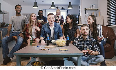 Mixed race friends watch sports on TV. Student football fans supporters get upset. Cheering for favourite sport team. 4K