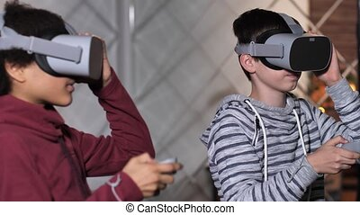 Close-up of diverse excited teenage boys wearing VR goggles and using joysticks during start of video game. Modern teens going to dive in virtual reality with help of augmented-reality headsets