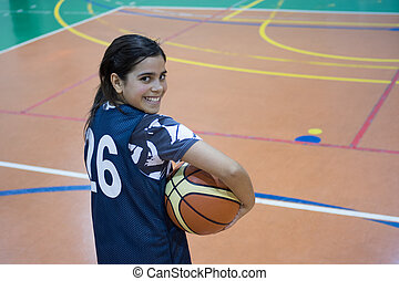 Mixed race girl in basketball court