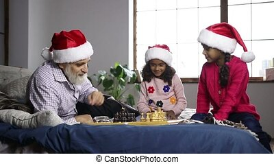 Mixed race girl playing chess with grandpa at home