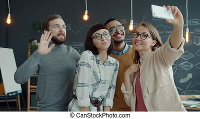 Mixed race group of people taking selfie with smartphone camera in creative office