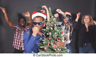 Mixed race group of young people at Christmas party. Slow...