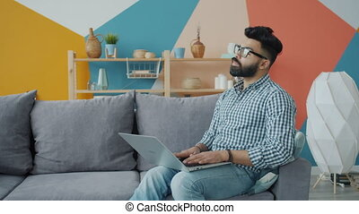 Mixed race guy in glasses and casual clothing is using laptop on sofa in apartment enjoying freelance work. Remote job, people and lifestyle concept.
