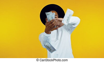 Mixed race hipster man with happy face scatters money. People overspend US currency. African man is flush with dollars on yellow studio background
