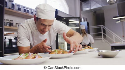 A professional mixed race male chef wearing chefs whites in a restaurant kitchen, putting food on a plate in slow motion