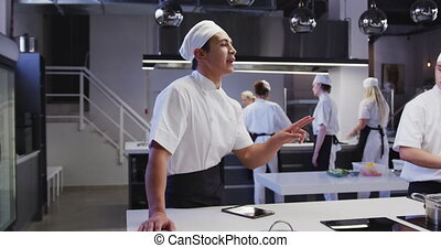 Professional mixed race male chef wearing chefs whites in a restaurant kitchen, using a tablet, with colleagues working in the background in slow motion