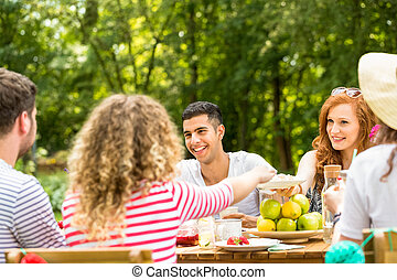 Mixed-race man and his friends sitting in the yard during a casual, summer meeting