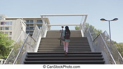 Mixed race man climbing stairs with a bike