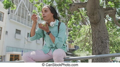 Mixed race man eating outside - Front low angle view of a ...