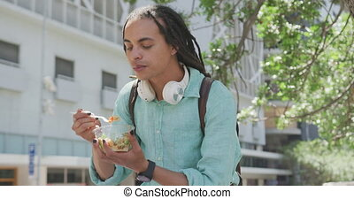 Mixed race man eating outside - Front view of a mixed race ...