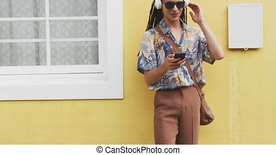 Front view of a mixed race man with long dreadlocks out and about in the city on a sunny day, wearing headphones and sunglasses, standing in the street, using a smartphone and smiling in slow motion.