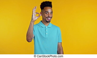 Mixed race man showing thumb up sign over yellow background...