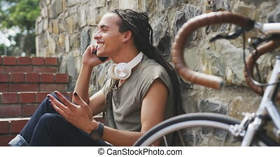 Side view of a mixed race man with long dreadlocks out and about in the city on a sunny day, sitting on the stairs in the street and smiling, using a smartphone, with his bicycle leaning against the wall next to him in slow motion.