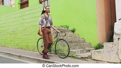 Mixed race man walking with a bike - Front view of a mixed ...