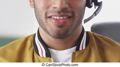 Front view close up of a happy mixed race man working in a creative office, wearing headset, talking and smiling