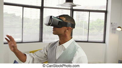 Side view of a mixed race man working in a creative office, wearing VR headset, looking around and touching virtual interactive screen