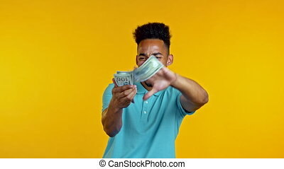 Mixed race man with happy face scatters money. People overspend US currency. African man is flush with dollars on yellow studio background