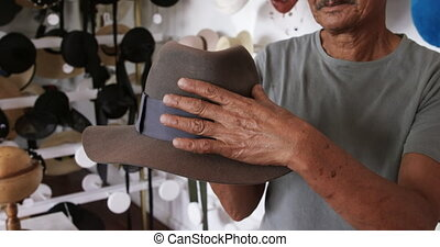 Mixed race man working at a hat factory - Front view mid ...