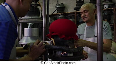 Mixed race man working at a hat factory - Side view of a ...