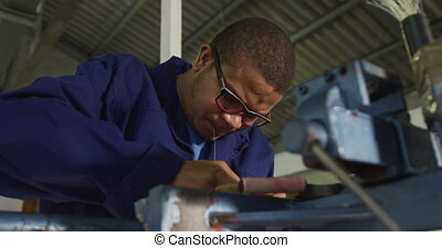 Mixed race man working in factory - Side view close up of an...