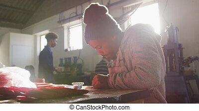 Mixed race man working in factory - Side view of an African ...