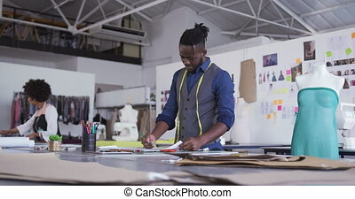 Mixed race man working in fashion office