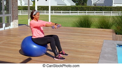 Mixed race mature woman exercising with dumbbells at backyard on a sunny day 4k
