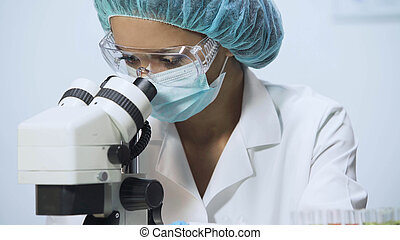 Mixed race medic looking into microscope, doing biochemical research, close-up