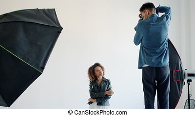 Mixed race model posing in studio while man photographer taking photos with camera